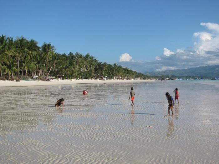 Çocuklar o kurtları topluyor. Biz küçükken çam ağaçlarından düşen fıstıkları toplardık. Bunlar da kumsaldan kurt topluyor.